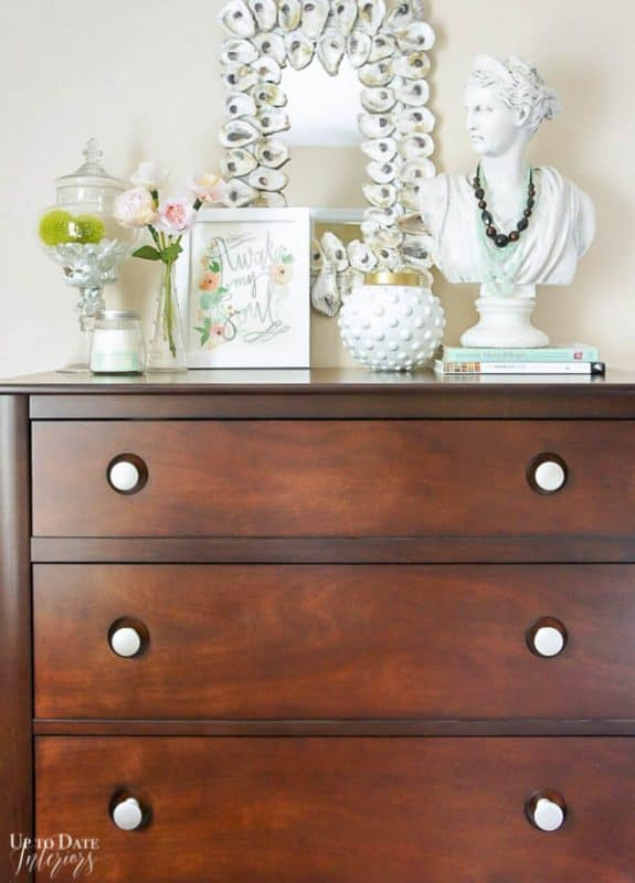 tall dark dresser with light decor on top including an oyster mirror and woman's bust