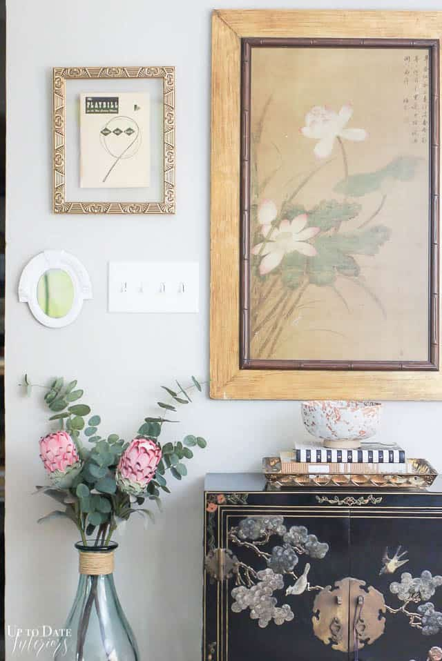 close up of bright with asian decor foyer vignette. black, pink, and gold