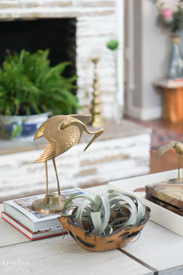 brass crane on top of books with a z gallerie coffee table in front of german schmear fireplace with fern