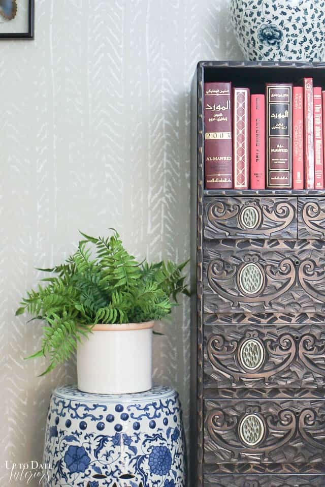 modern stenciled gray wall with asian cabinet and garden stool, red books, and fern