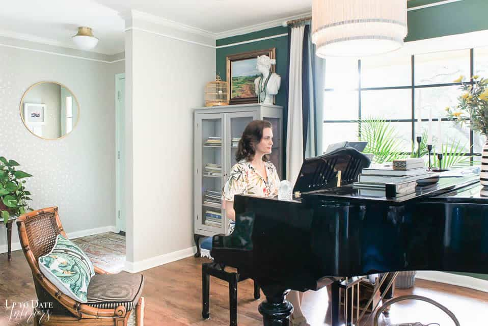 girl playing piano with green focal wall and fringe floor lamp. Eclectic glam maximalist style.