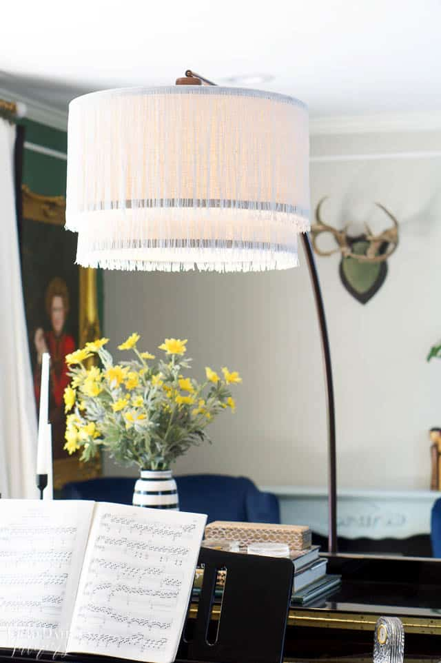 close up of fringe lamp over piano and antlers on the wall in the background. Yellow flowers in a black and white striped vase. Portrait of woman .