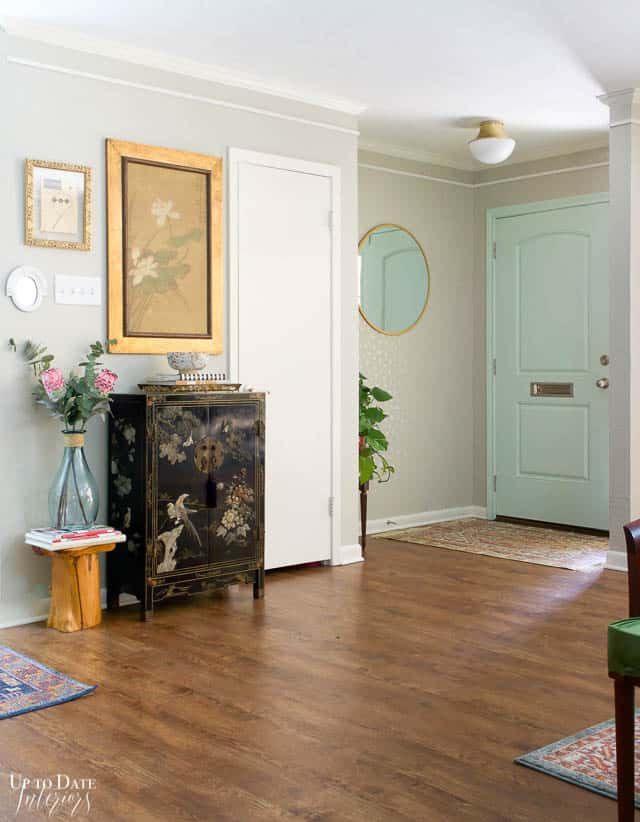 bright foyer with asian decor and mint green front door in an eclectic home no shoes in the house sign