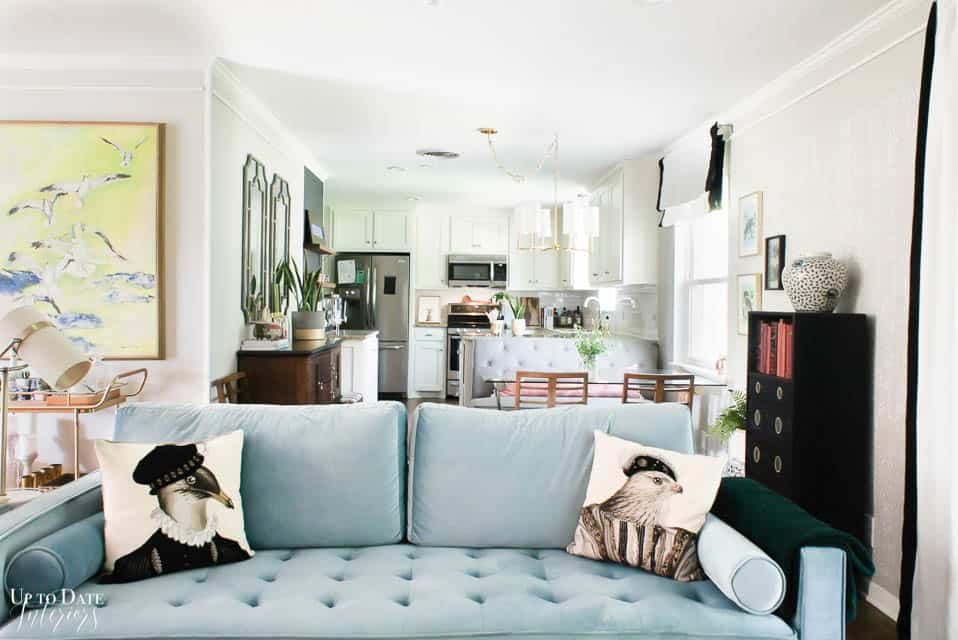 blue sofa with jules pules bird pillows and kitchen in background