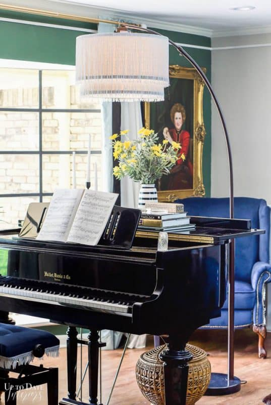 lamp with fringe over grand piano in front of picture window with a green wall and blue velvet chairs
