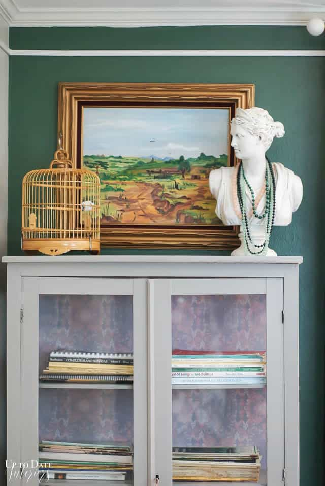 music cabinet in front of green wall with oil painting, bird basket, and woman's bust wearing necklaces