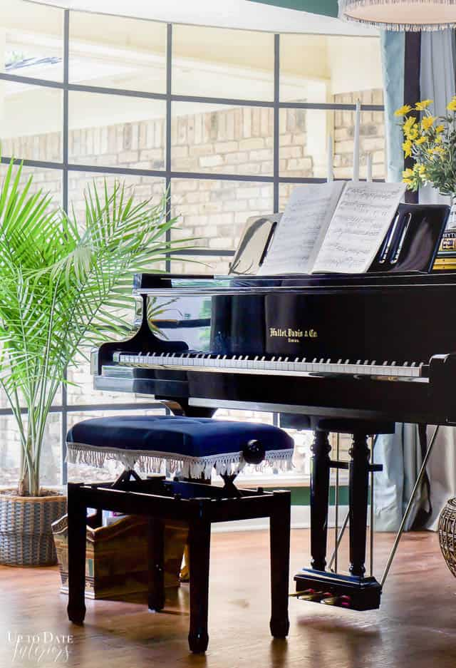 piano bench upholstered in blue velvet with white trim with grand piano in front of picture window and palm tree