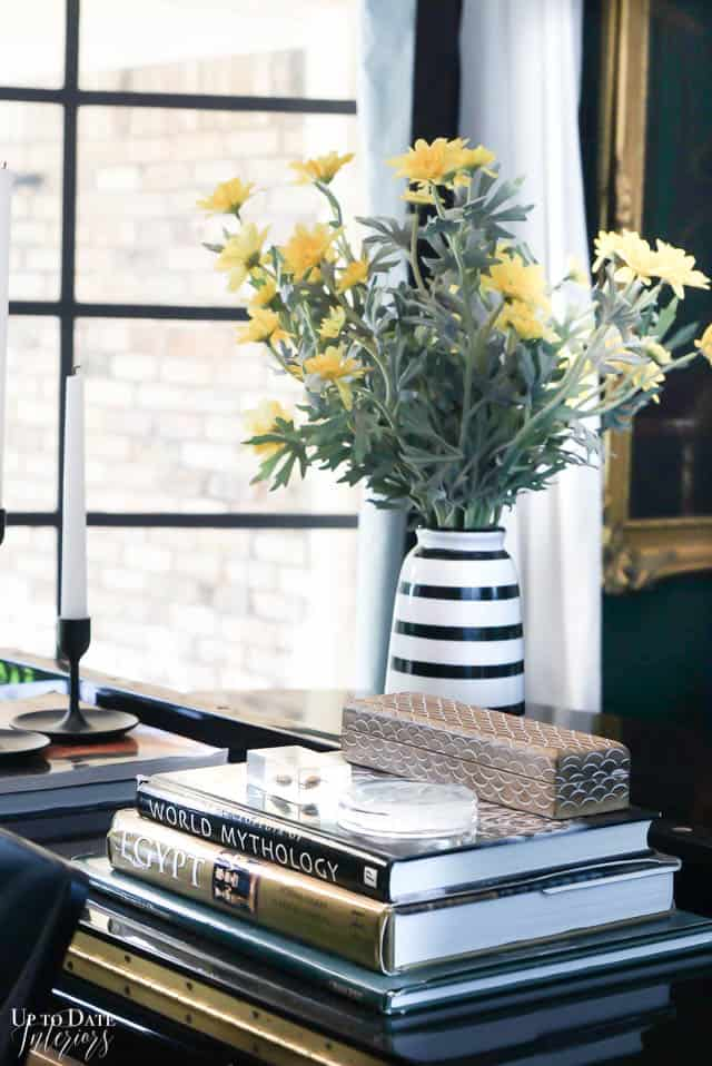 yellow flowers in striped vase on piano in front of window