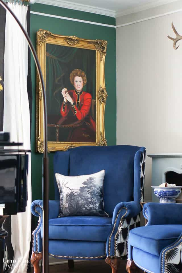 woman's portrait on green wall with two blue velvet chairs and tropical neutral pillows
