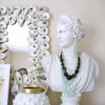 Rectangle oyster shell mirror with vase and woman's bust on books.