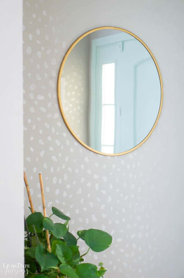 round mirror on gray spotted wall