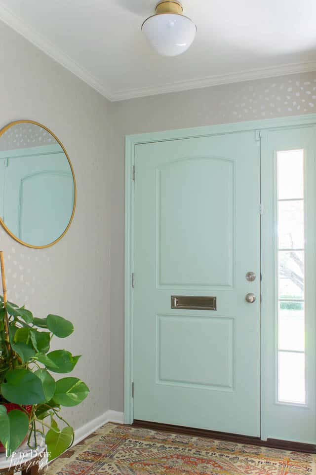 mint green interior front door and gray with metallic spots stenciled entryway walls. Green plant and lots of light