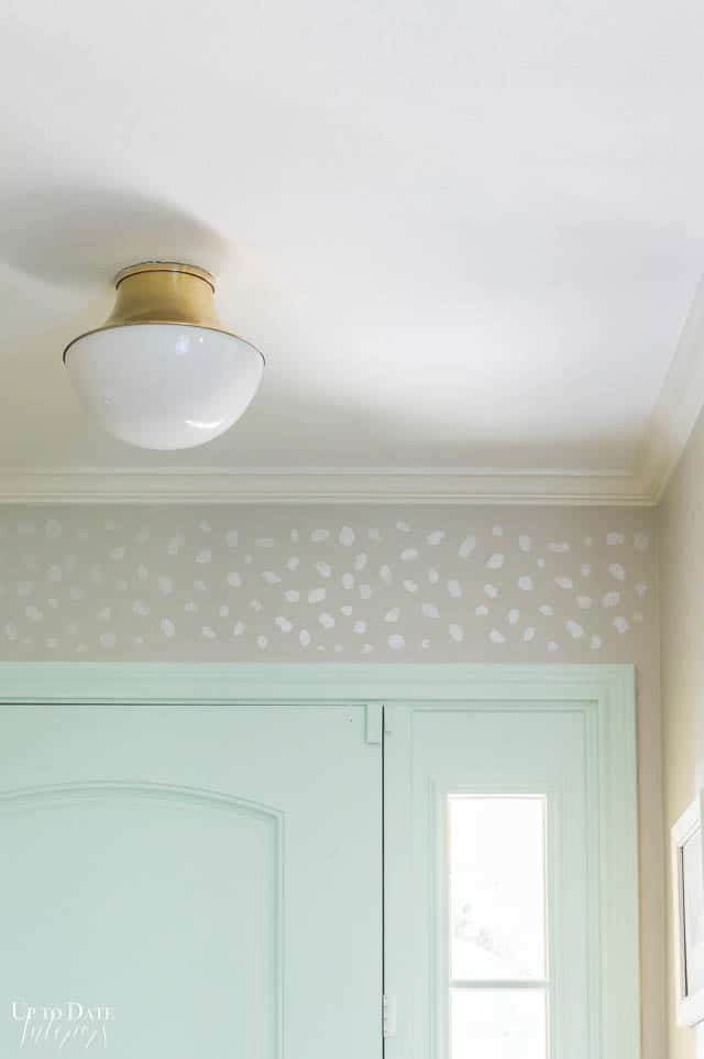 Stencil Wall Foyer Makeover with gold and white flush light and mint green door close up