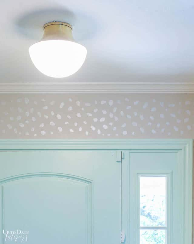 gray stenciled entryway with mint green door and flush mount gold light