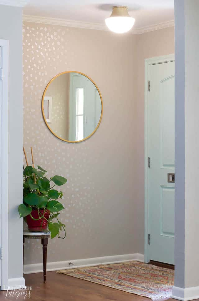 bright and airy entryway with mint door, round mirror, plant, and gold and white flush mount modern light fixture