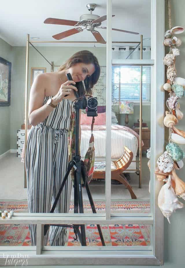 girl taking pictures in an eclectic home summer bedroom