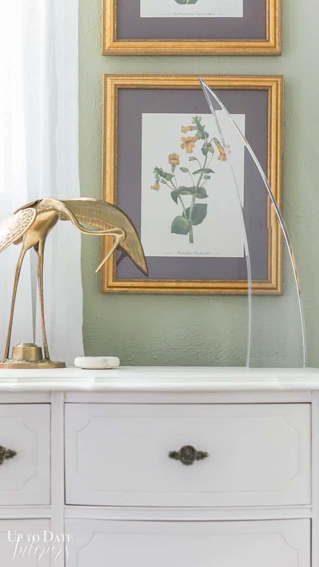 close up of botanical art, brass crane, and lucite sculpture on top of a dresser