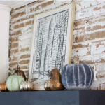 Faux Heirloom Pumpkins on a black mantel with painting