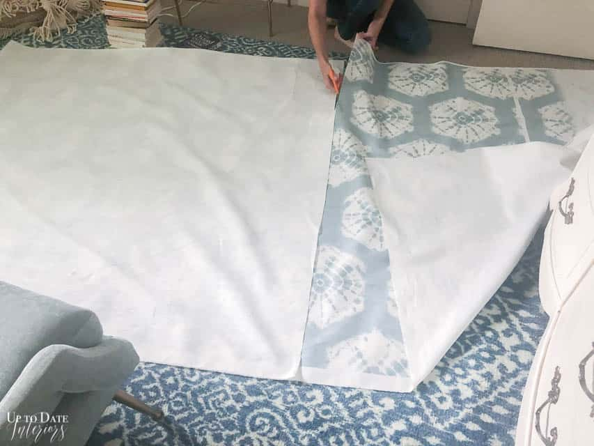 Cutting blue fabric for a fringe bed skirt