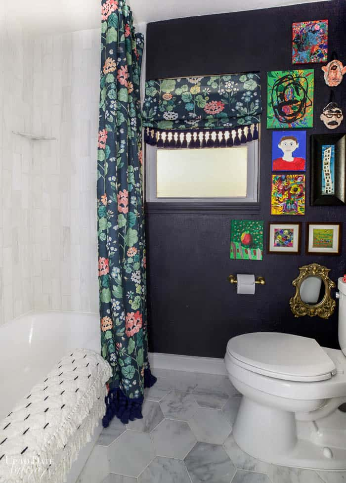Dark moody wall in bathroom with colorful art and floral shower curtain and roman shade. White marble bathtub surround and white marble floors.