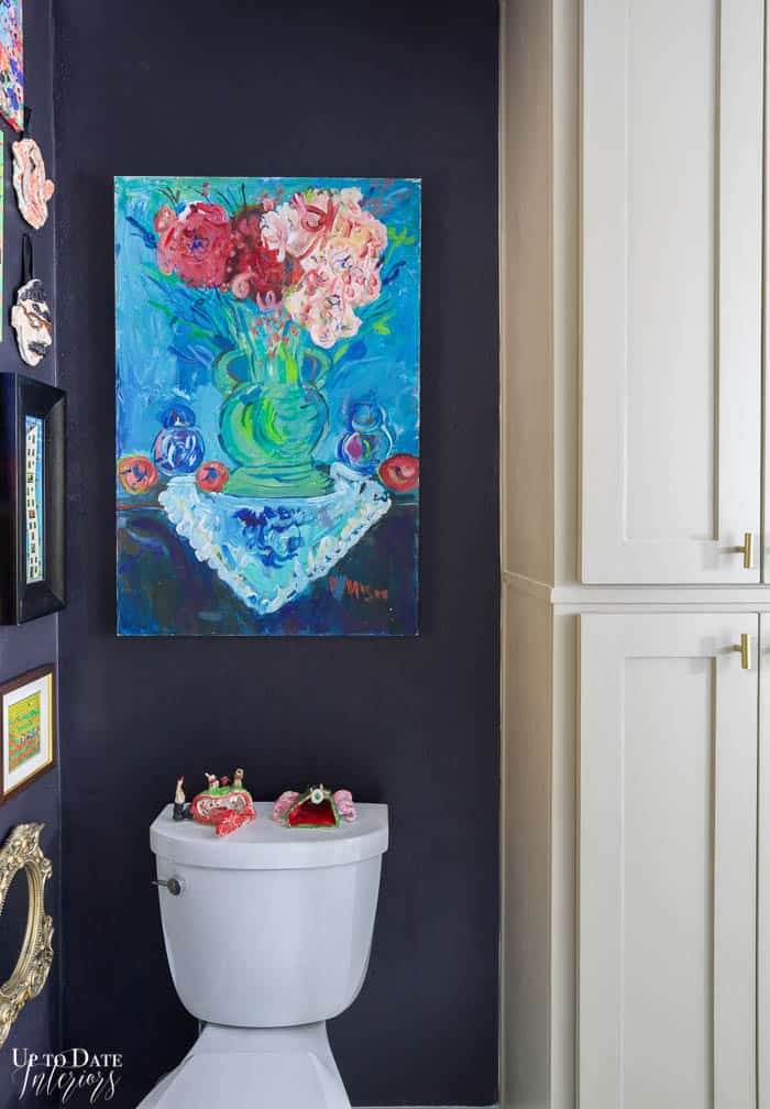 Bold blue floral large painting over toilet and next to tall taupe cabinets. Black wall paint.