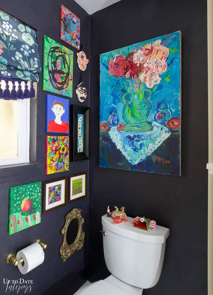 Art corner next to toilet with black wall paint and colorful gallery wall.