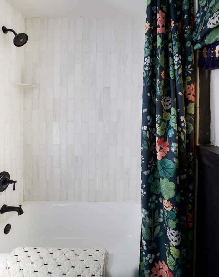 Dark moody bathroom with view of tub and white marble vertical tiles, black faucet, black wall, and dark floral shower curtain.  Black and white bathroom rug draped over tubside.