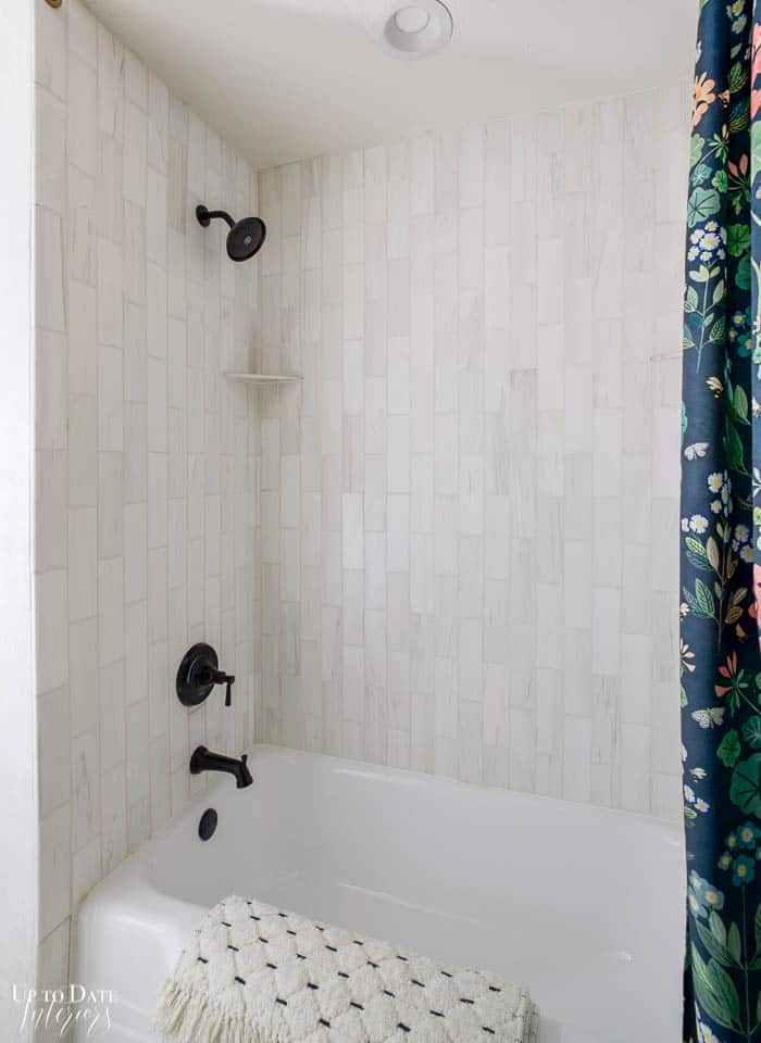 White vertical marble tile bathtub surround with black faucet and trim.  Dark floral shower curtain.