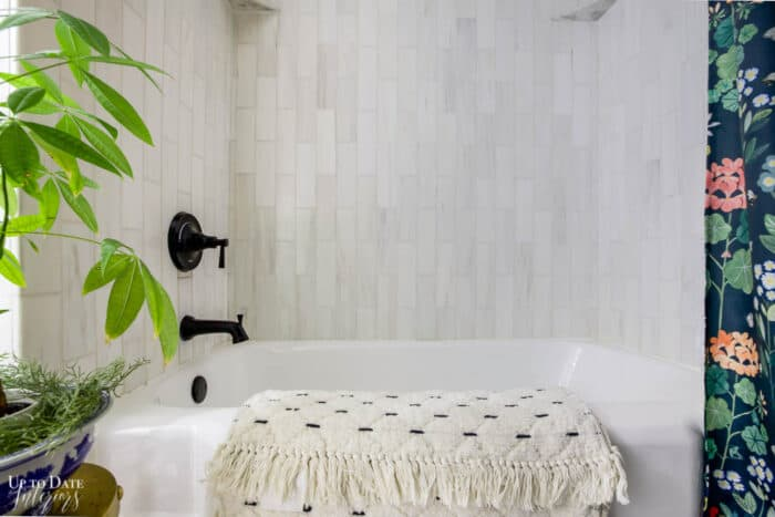 Marble Bathroom with cast iron tub and vertical marble tile surround.  Black faucet and trim.