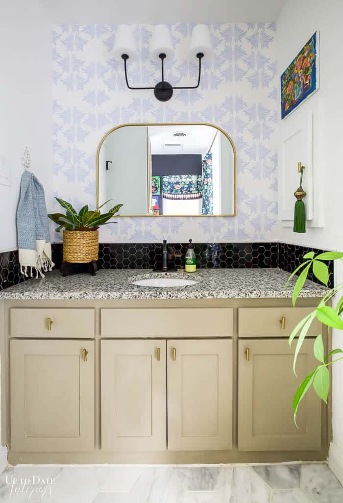 Marble Bathroom Reveal with blue and white wallpaper in vanity area, granite counter, taupe cabinets, and black marble backsplash.  White marble floors.