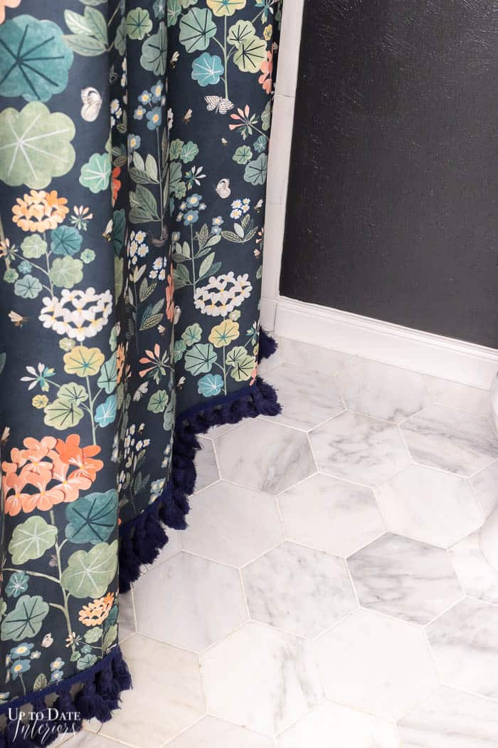 White marble bathroom floors with floral shower curtain and tassels against a black wall.