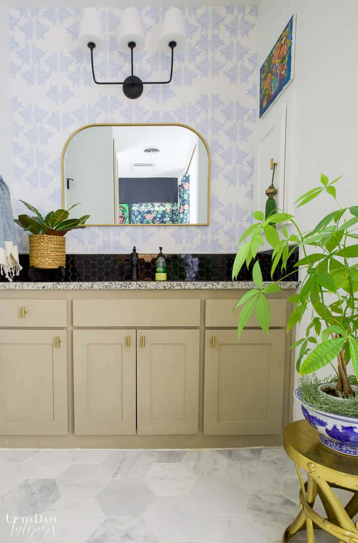 Marble Bathroom Reveal Vanity side with taupe cabinets, black faucet and marble backsplash, blue and white wallpaper and bright white walls and marble floor.  Gold accents and plants.