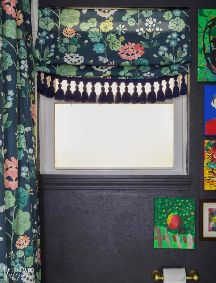 Dark moody wall in bathroom with small window and floral roman shade and shower curtain. Glimpse of colorful art.