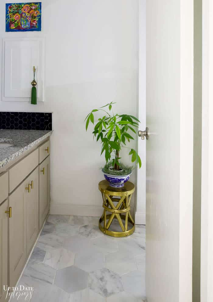 View into hall bathroom with white hexagon marble floors, white walls, and grey cabinets.