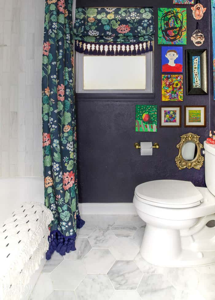 Black bathroom wall with colorful art and floral shower curtain and roman shade with tassels.