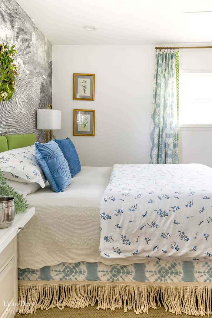 Fringe bedskirt with blue and white bedding and green accents side view
