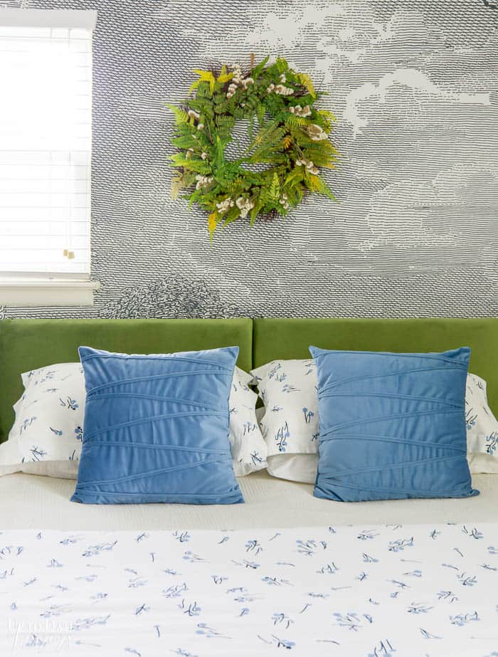 Summer Bedroom Decorating with a dried fern wreath over a green velvet headboard and blue velvet throw pillows.