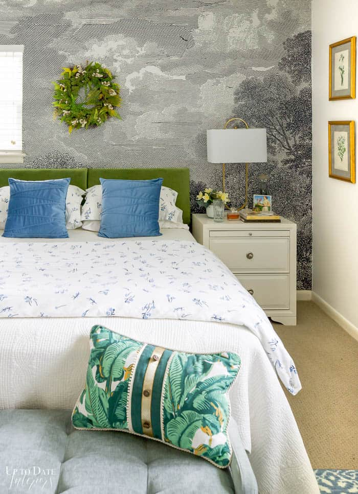 View of bed with a bench at the foot of the bed and botanical pillow.  Mural focal wall with green headboard and green wreath.