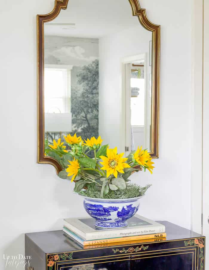 Gold mirror behind sunflowers in blue and white china bowl on a stack of books in the bedroom.