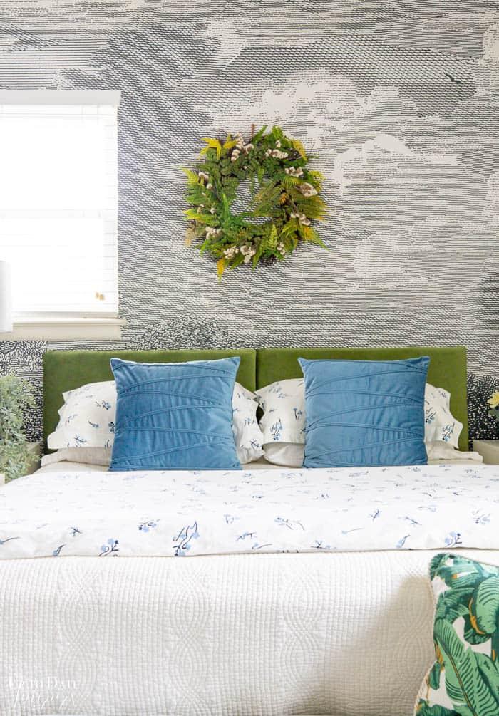 Green velvet headboard with blue velvet pillows on white bedding in front of a black and white mural.
