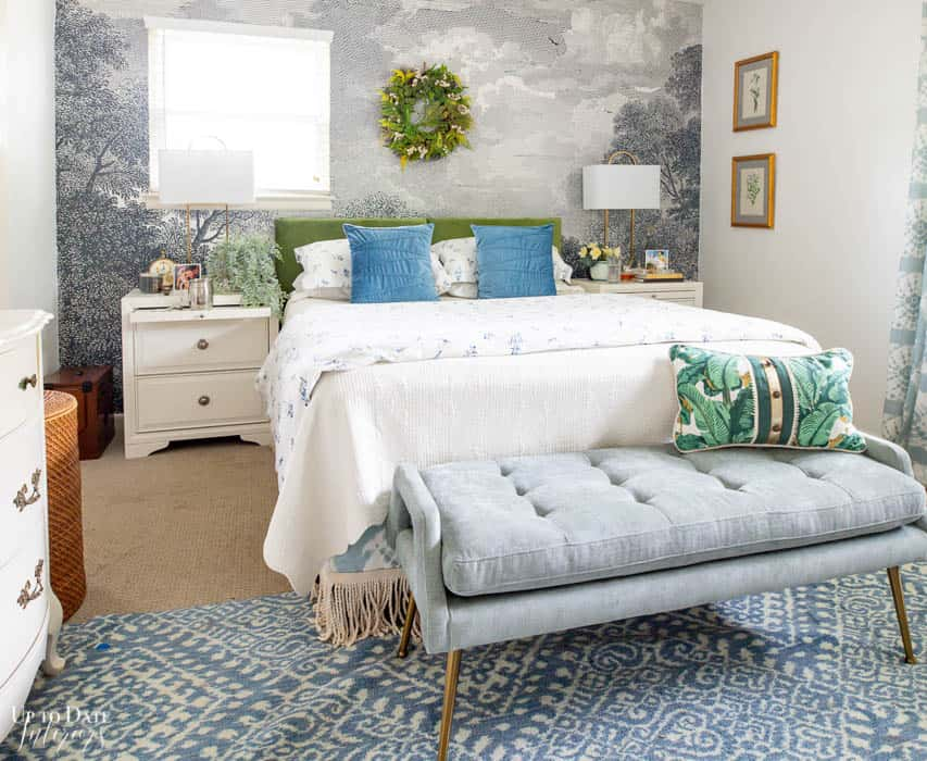A wide view of a blue and green bedroom decorated for summer with a wreath on the wall.