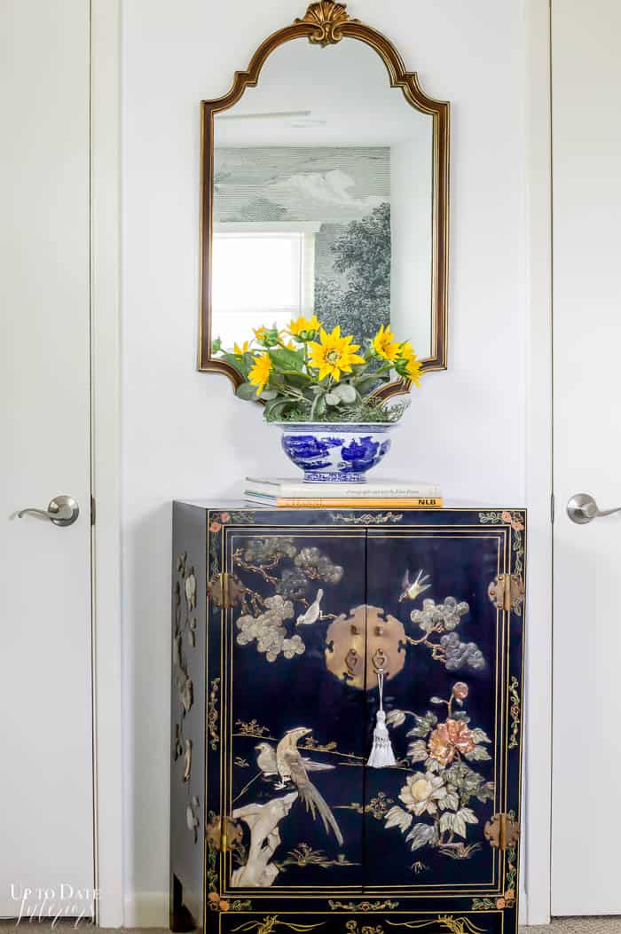 Black Asian Cabinet with Flowers and a mirror above between two white closet doors