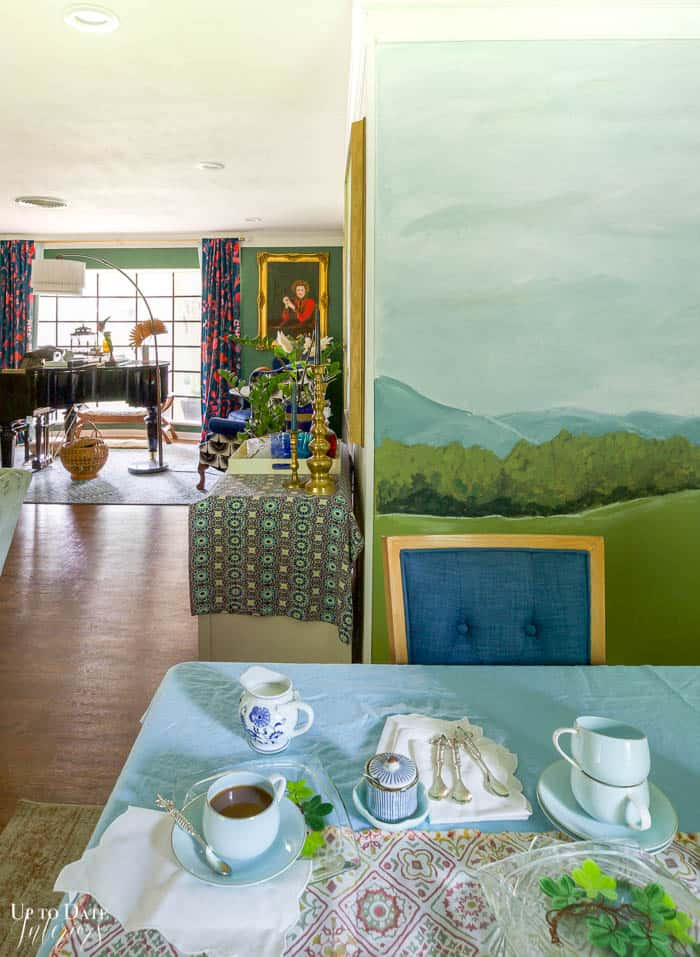 landscape wall mural and view into piano studio from dining area