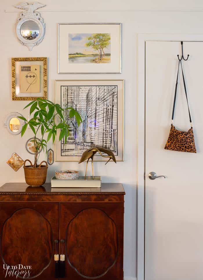 Foyer dark wood cabinet and light artwork.