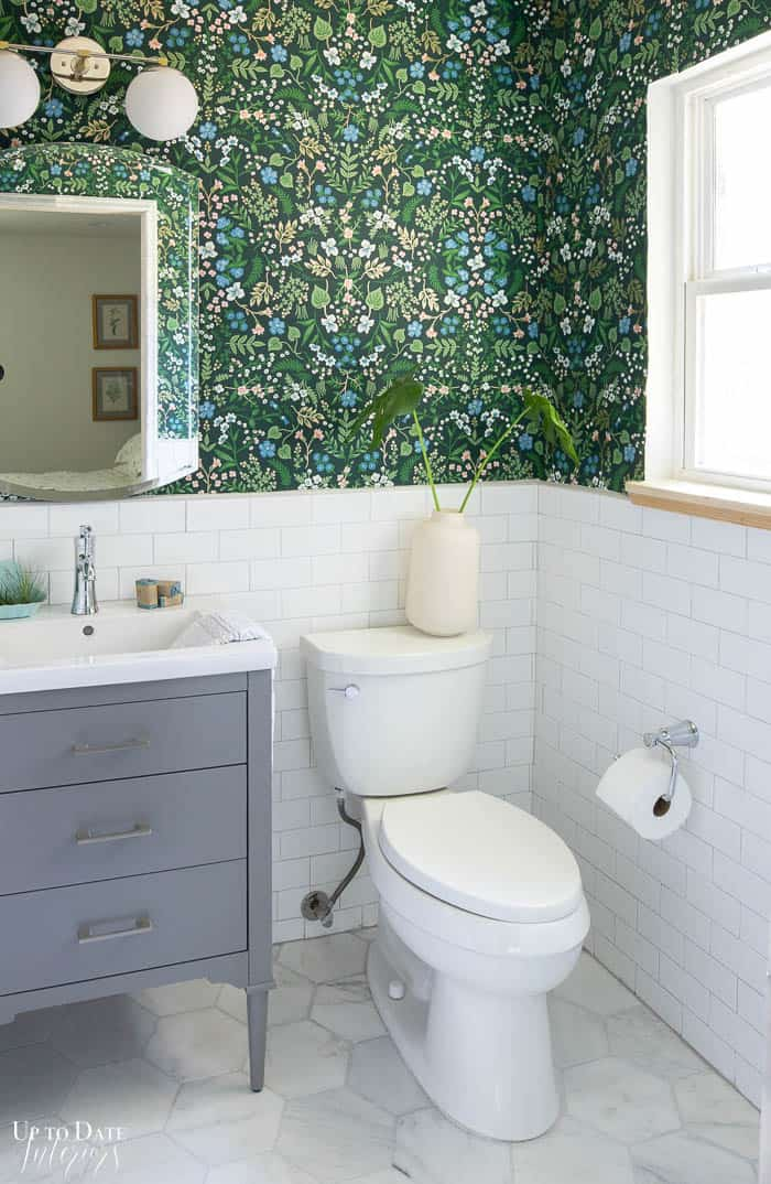 White And Grey Bathroom with green floral wallpaper.  Grey vanity and marble floors. White subway tile wainscotting.
