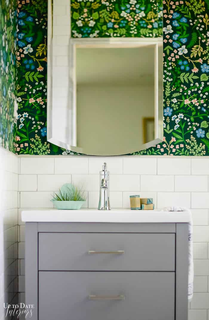 dark green floral wallpaper with tile wainscotting behind a grey free standing vanity.