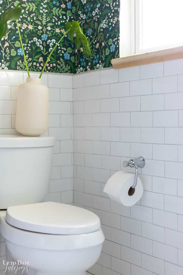 white tile with chrome toilet paper holder next to  toilet.  Pop of green floral wallpaper on the wall.