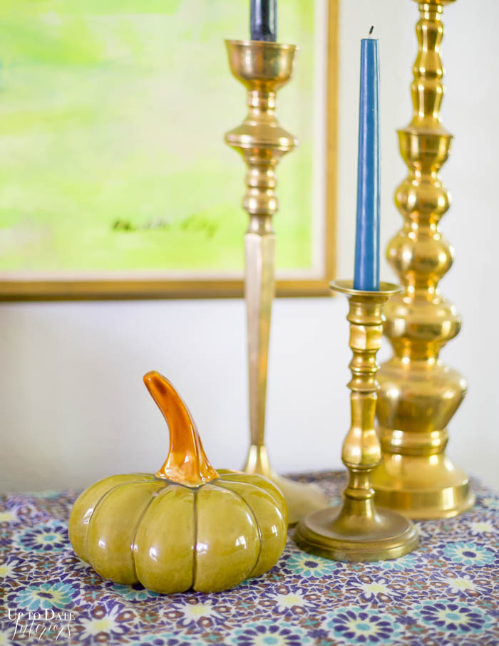 Glass green pumpkin on blue tablecloth with brass candlesticks